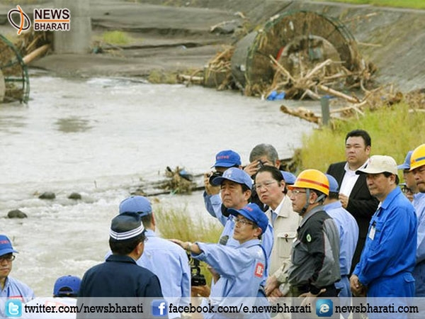 Japan PM Abe cuts down time from European tour, visits flood-hit southwest Japan